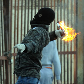 A Nationalist youths throws a petrol bomb at police in the Ardoyne area of north Belfast July 12, 20